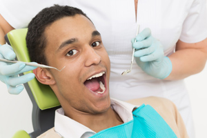 Portrait of young man sitting with his mouth opened while having examination of his teeth at dentist's office.