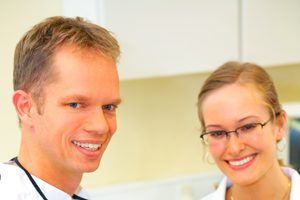 Dentist and assistant with smiling patient in dentist's office